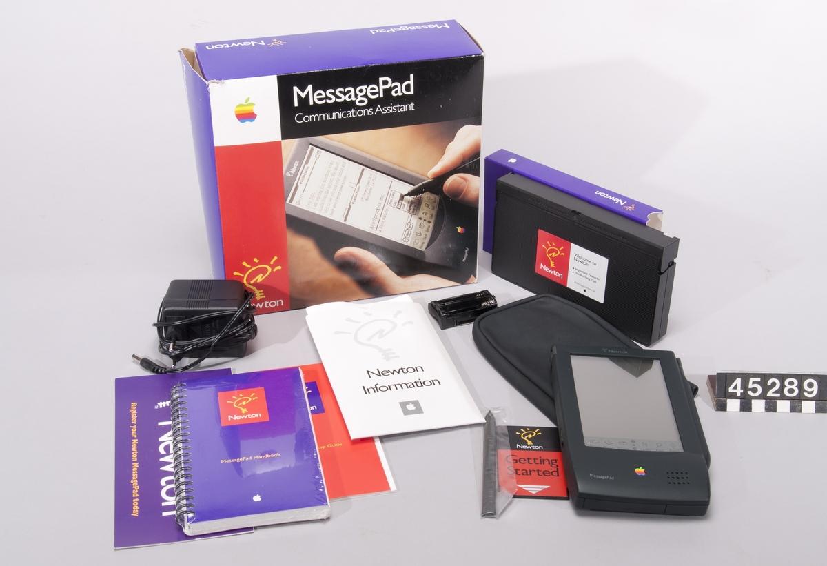 """Newton MessagePad i originalförpackning innehållande nätenhet, bruksanvisning, instruktionsvideo samt extra penna.  Typ H1000, nr. S33337J5  4MB RAM, 640K ROM Port för att ansluta extra minne, kommunikationskort för personsökarsystem. Svart/vit tryckkänslig flytkristalldisplay. Teckenigenkänning med """"Newton pen"""". Funktioner som adressbok, anteckningar, uppringningsssistans, kalender. Synkronisering med dator. Med tillhörande modem kan MessagePad sända fax och ansluta till servrar för """"electronic mail""""."""