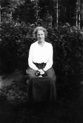 Sittande kvinna med blommor i handen. fb82c0c801f3c