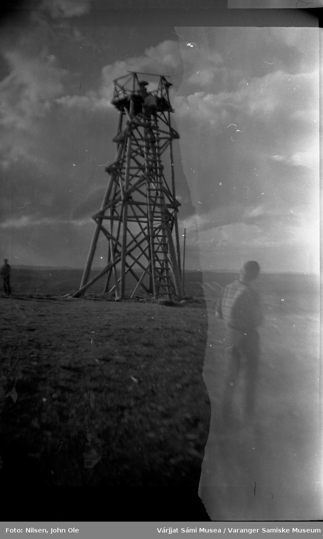 Muligens et utkikkstårn. En mann står med ryggen til i forgrunnen og en annen mann klatrer opp i tårnet. Ukjent sted 9. juli 1966.