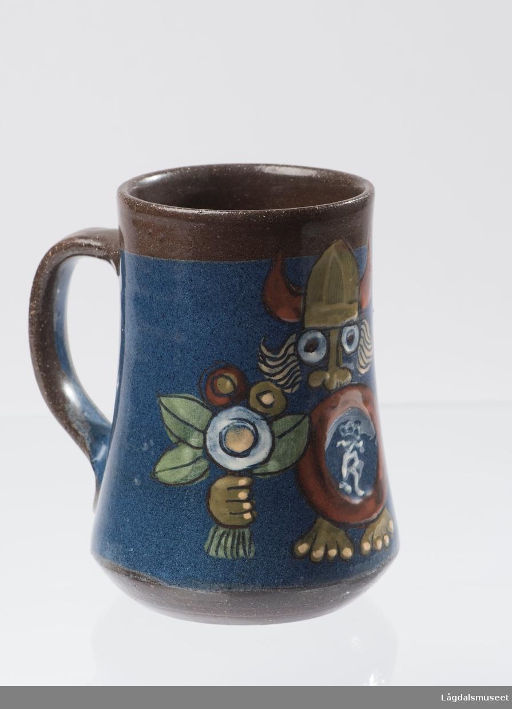 Ølkruset viser et motiv av en viking med logoen til Kongsberg Våpenfabrikk avbildet på skjoldet. Vikingen holder en bukett blomster i andre hånden.