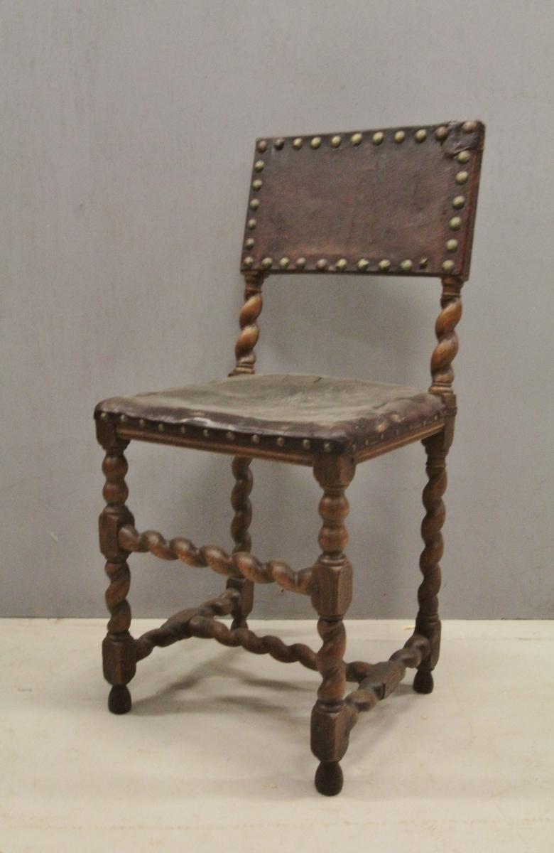 Trestol med skinntrukket sete og rygg. Beina rette med slynget fasong (ligner spiralsøyle), forbundet med H-sprosse og 1 vertikal sprosse foran (også spiralsøyle formede sprosser). Skinnet er naglet fast til treverket.