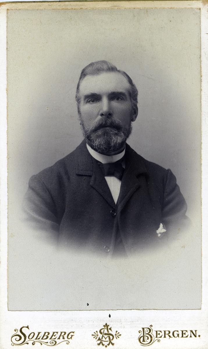Portrett i halvfigur av en mann. Mannen er iført smoking med en mørk frakk utenpå. Mannen har et tørkle i jakkelomma.