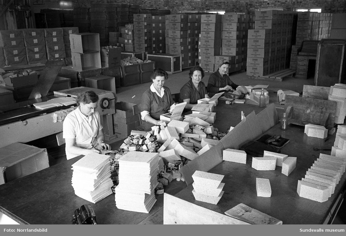 Nyhamns kemiska fabrik drevs 1947-1985 i före detta Nyhamn Cellulosa AB:s lokaler. Bilder från verksamheten där ett arbetslag med kvinnor sorterar och packar cellulosasvamp, Svabo. På första bilden syns från vänster: Stina Åman, Göta Horn, Rut Andersson och Hulda Andersson. Cirka 3000 golvmoppar. tvätt- och disksvampar per dag förpackades och en stor del av produktionen gick på export, främst till Japan och Tyskland.