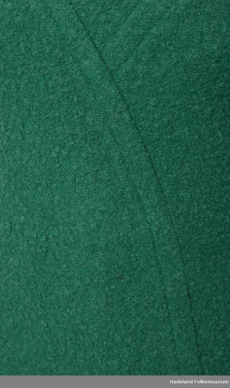 Kjole, kvinne. Selskapskjole. Grønn, boucle, Ull, trikot. For av kunstsilke. Sidelommer og søm midt bak med glidelås. Panelsømmer ned i spiss foran, den ene forlenget helt ned. Båtutringning. Uten ermer.