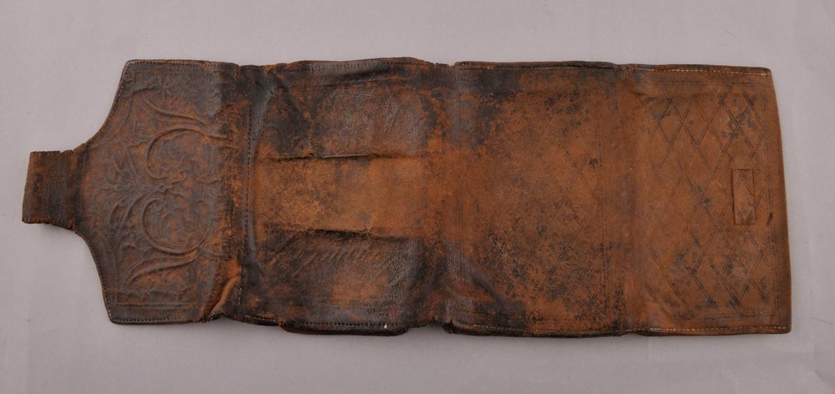 Veske av skinn med trykt mønster og ornament.