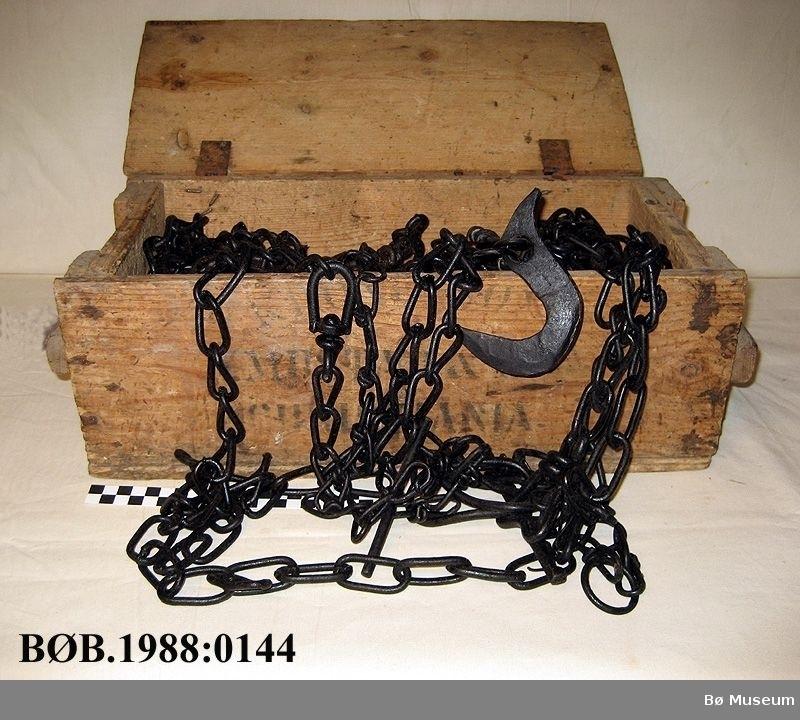 Trekasse med diverse jernreidskap, bl.a. kjetting, grev, hestesko og kuband. Trekassa har hengsla lok.