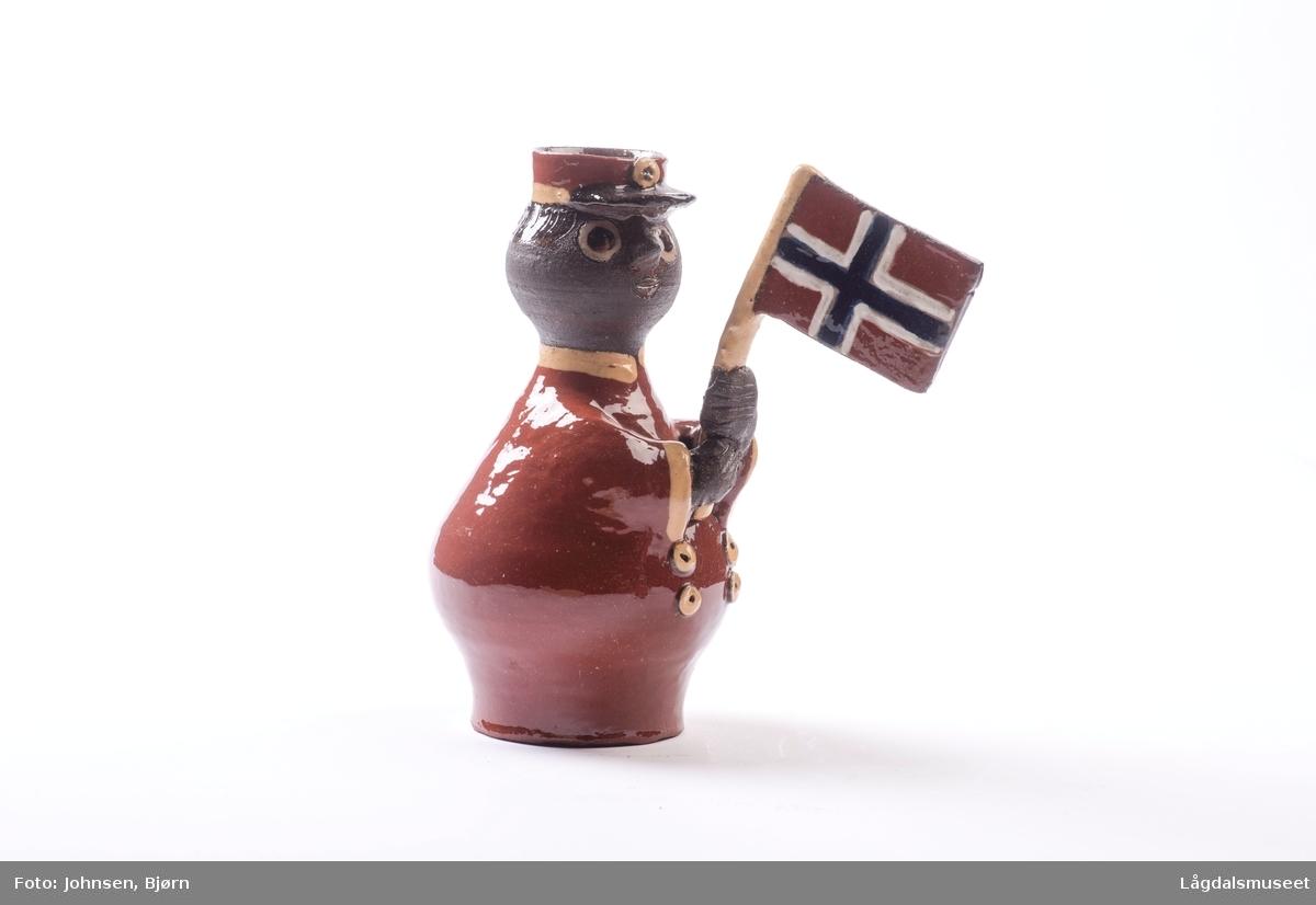 Dekoren på lysestaken utgjør klærne til flaggbæreren. Utforelsen er en mann med uniform og flagg.