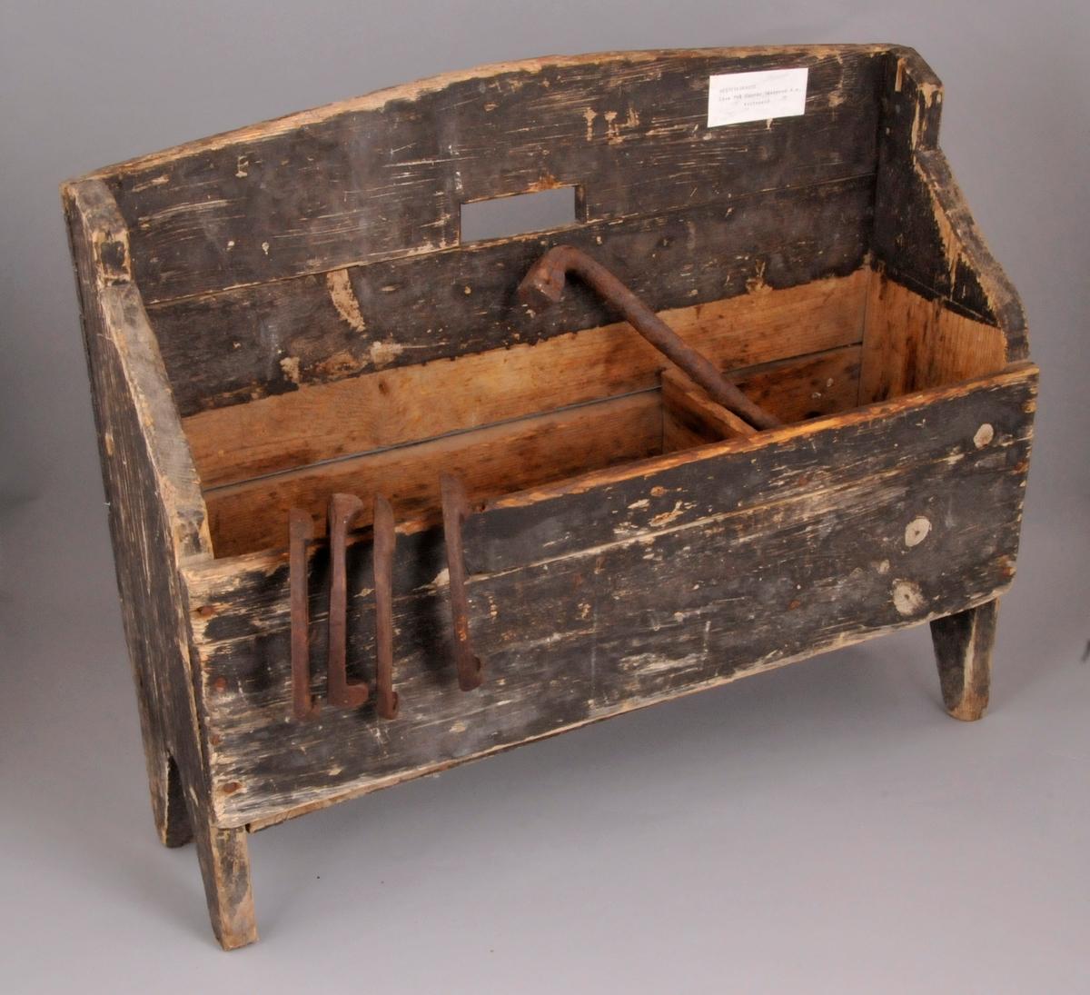 Skokasse/verktøykasse, inndela i to rom, står på føter, måla utvendig. Inneheld hestesko og verktøy.