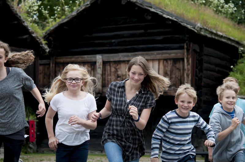 Gruppe barn og unge løper i Friluftsmuseet