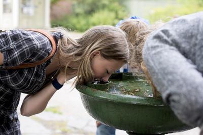 Tre ungdom drikker av vannfontenen i Gamlebyen. Foto/Photo