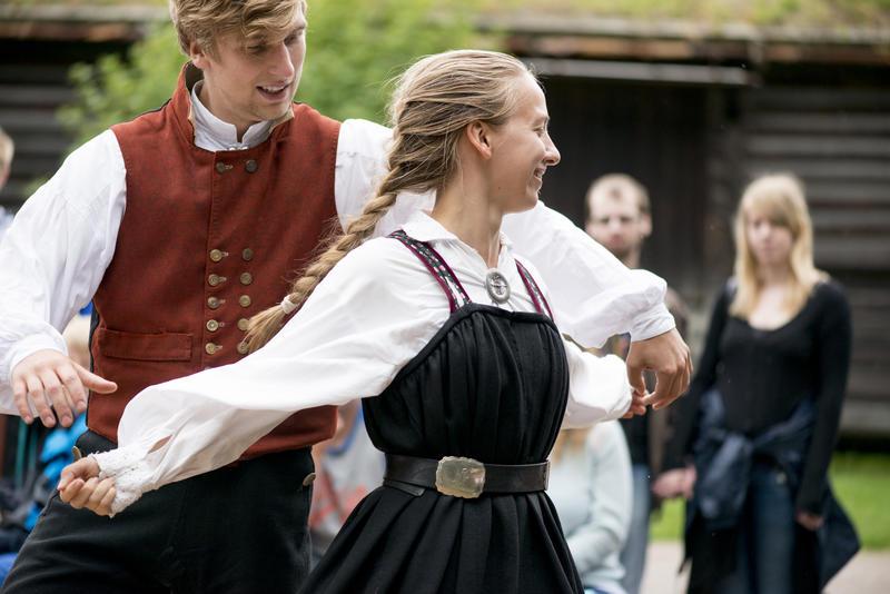 Man og kvinne i folkedrakt danser folkedans