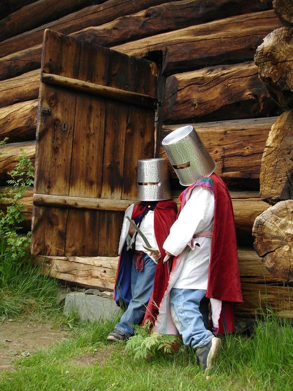 to barn ved en tømmerkoie, metallbøtter på hodet, laget som hjelm med tittehull, røde kapper på.