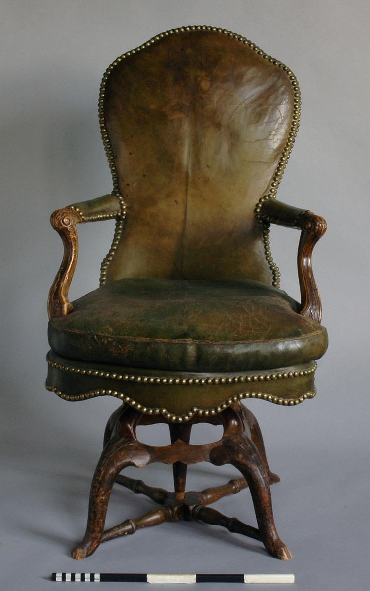 Länstol av trä, vridbar, med lös dyna, klädd med grönt skinn.