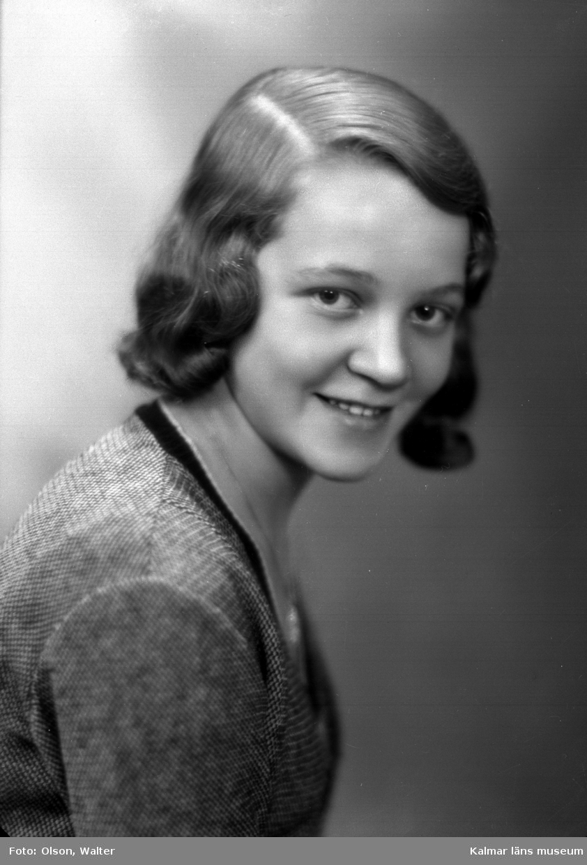 Ateljébild på en kvinna men jumper och halsband med hänge. Enligt Walter Olsons journal är bilden beställd av Märta Meijer ifrån Fabriksgatan 25 b i Kalmar.