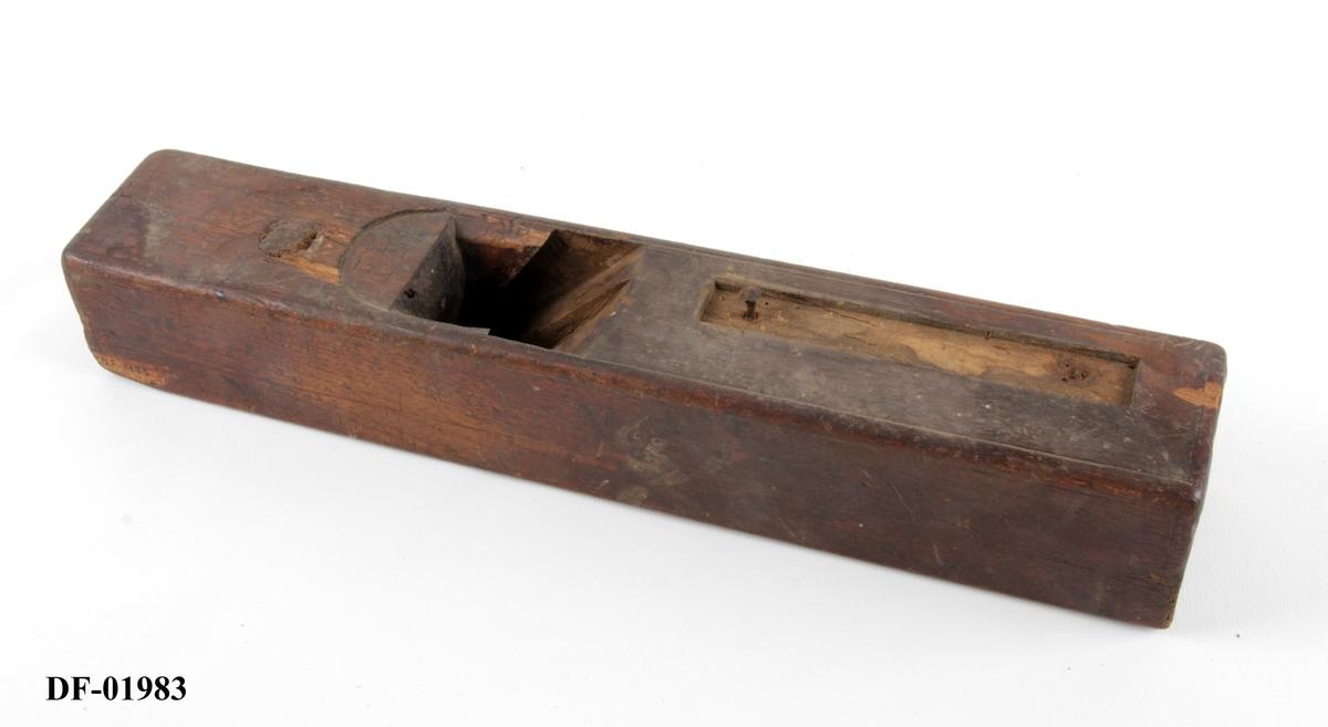 Høvelstokk med flat såle. Nedbanket rund stillingsknapp av tre. Spor for håndtak på høyre side. Vinkelseng på 44 grader. Sponåpning 5,7 cm x 1,4 cm.