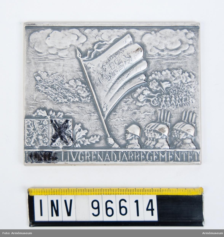 Plakett i silver för Livgrenadjärregementet. Plakett, åtsida enligt modell av Karl Hultström, fanvakt jämte kavalleri och artilleri i strid samt Östergötlands och Smålands vapen samt inskription KUNGL. LIVGRENADJÄRREGEMENTET. Stans nr 10876, 10877. Stans härdad 1938-06-29.