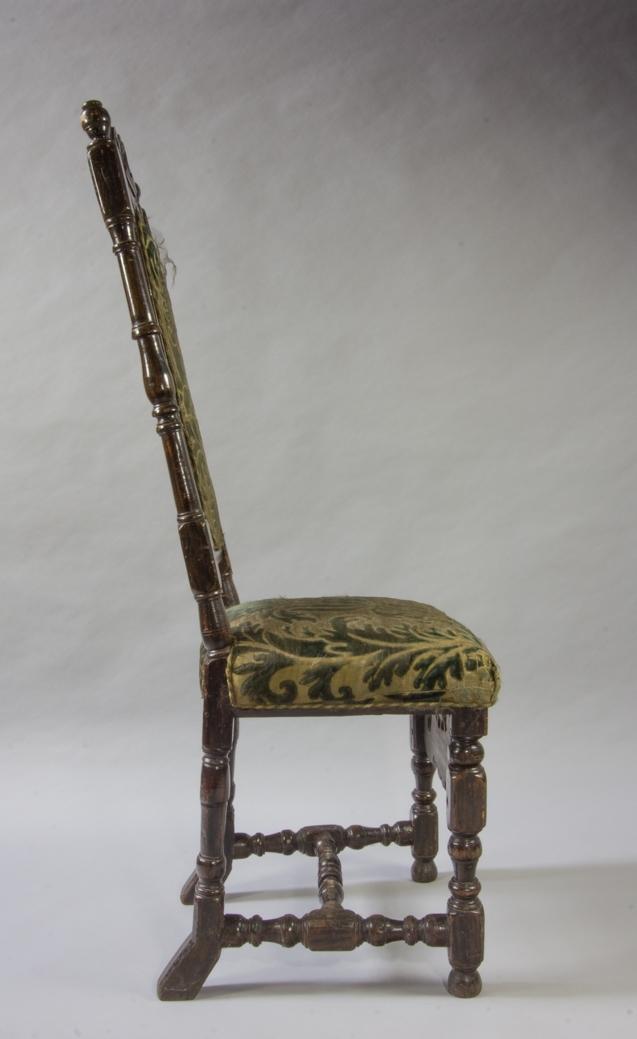 Stol av trä, med vertikal ryggbricka, målad i brunt. Profilerat överstycke med rocaille och svarvade ryggstolpar.  Fyra profilerade ben och H-kryss. Främre sargen dekorerad med skuren rocaille. Framslån rikt skulpterad. Ryggbricka och sits klädda med mönstrad sammet i grönt och gult. Grön och gul snodd runt ryggbricka och sits. Ryggbrickans baksida och undersida klädda med linnetyg.