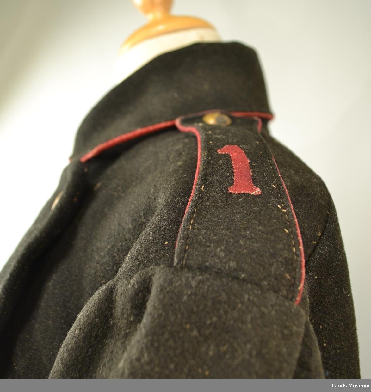 Kappen er halvforet med blå boy. Røde biser på krave og skulderkraffer, spendsel i rygg med 4 messingknapper. Skulderklaffer med 1 messingknapp på kvar side. Foran 2 rader messingknapper - 9 i alt. Tallet 5 (fem) er innslått på knappene. Oppslag på ermene.