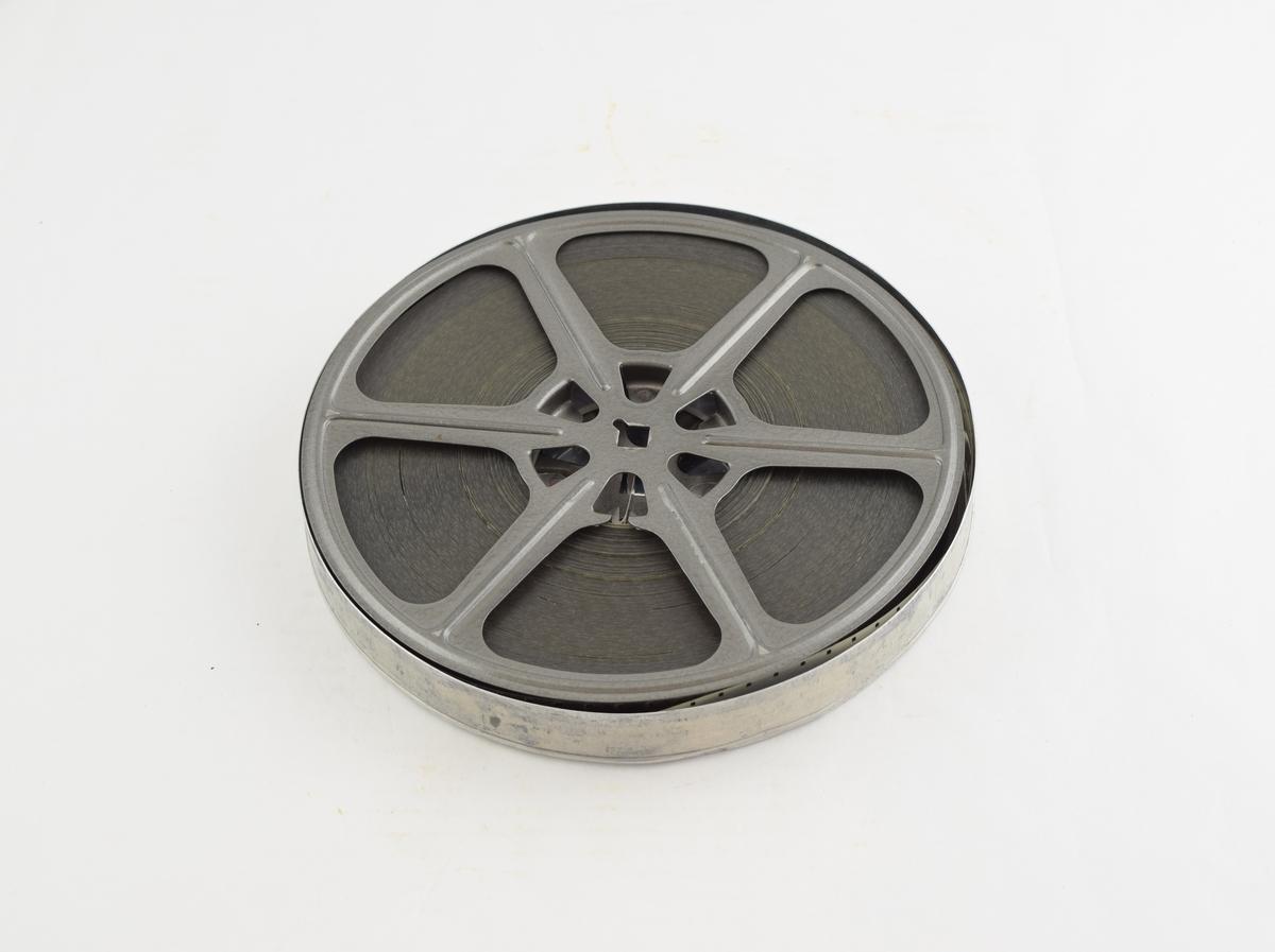 Filmrull i eske. Film på metallspole. Rundt metalletui i to løse deler: bunn og lokk.