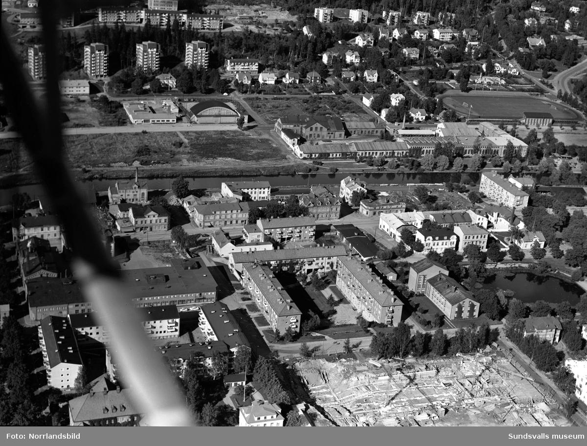 Flygfoton över västra Norrmalm med Alliero, tennishallen, Epidemin, Sundsvalls verkstäder. Påbörjat bygge av bostäder vid Ludvigsbergsvägen 12-20 och på en av bilderna syns det påbörjade bygget av Åkersviksskolan i nederkanten.