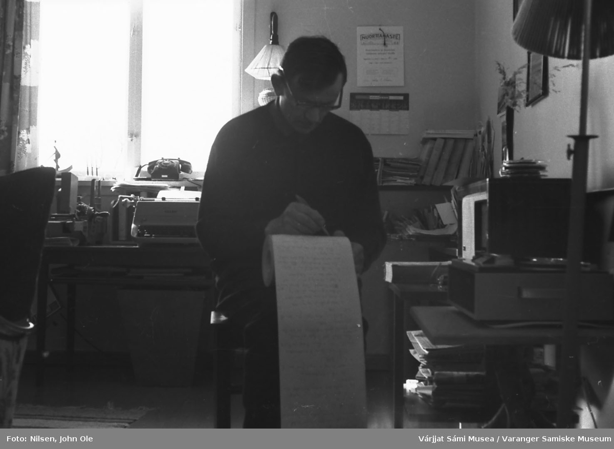 Tidligere redaktør i Nuorttanaste John Ole Nilsen hjemme i kontorkroken sin i Bunes. Sannsynligvis holder han på å skrive noe i forbindelse med utgivelsen av neste nummer av Nuorttanaste. Til venstre ses skrivemaskinen han brukte mye. Til høyre den gamle radioen han lyttet mye til. 1967