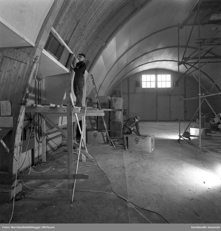 Två män jobbar med att isolera i pjäshallen vid LV5.