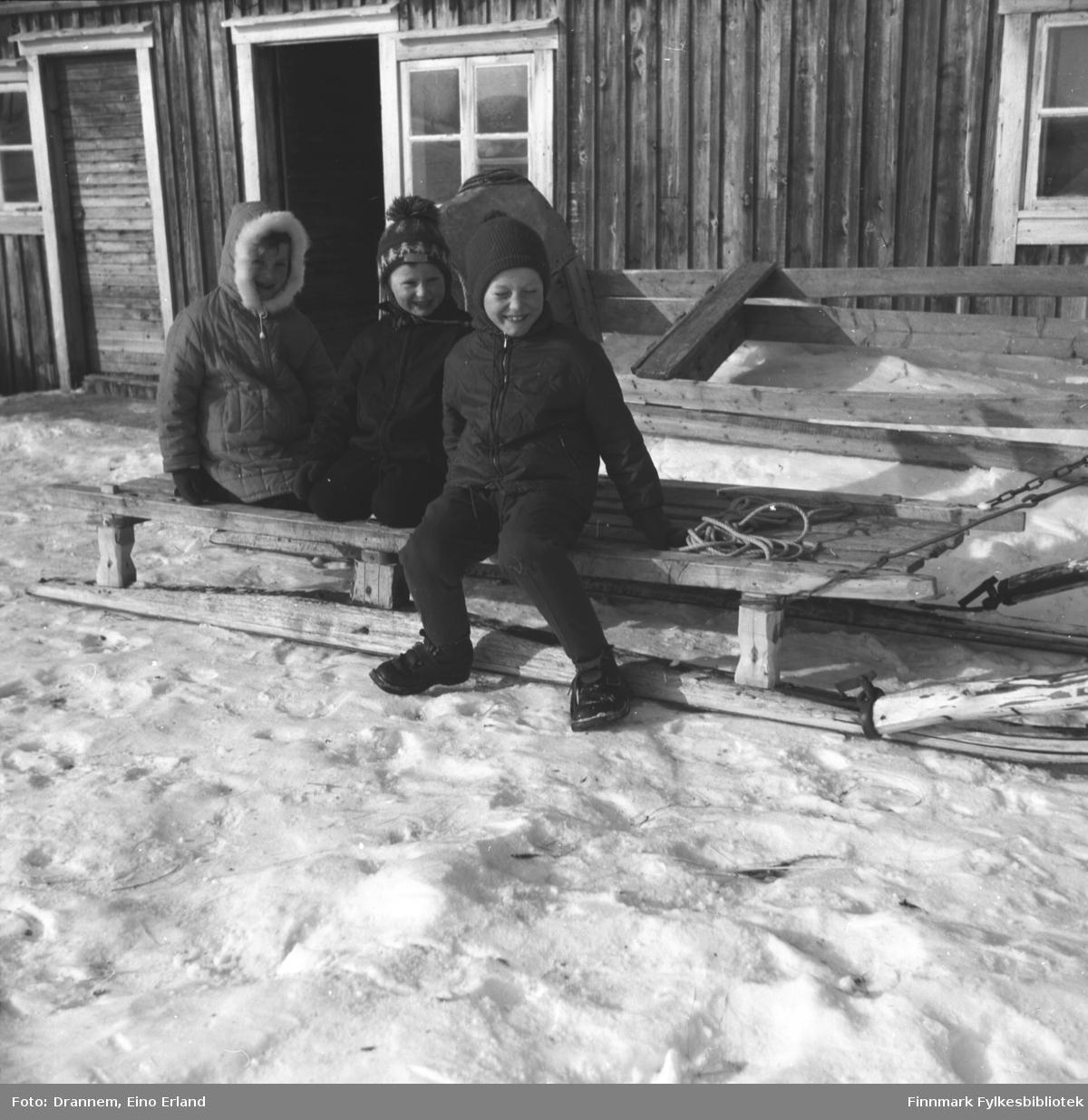 Tre barn sitter på en slede utenfor en bygning. De er fra venstre: Kari, Hans og Ole Gabrielsen.