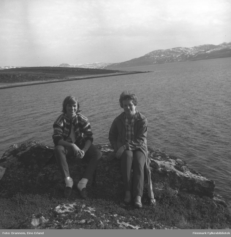 Marit Gabrielsen og Turid Karikoski sitter i veikanten til Rv94 like utenfor Hammerfest. Kargeneset ses i bakgrunnen.