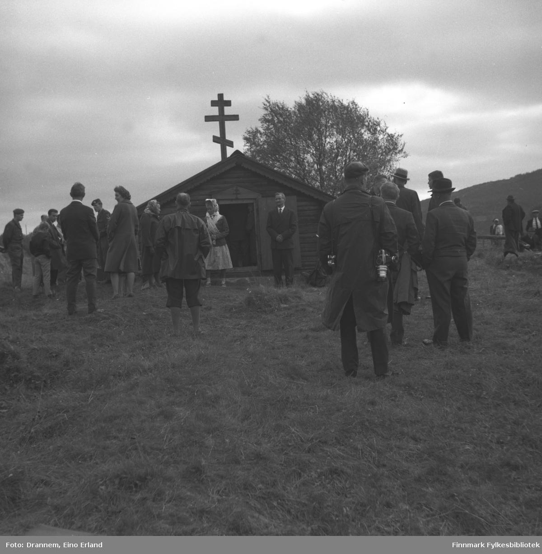 En del pentkledte folk fotgrafert rundt kapellet i Neiden.