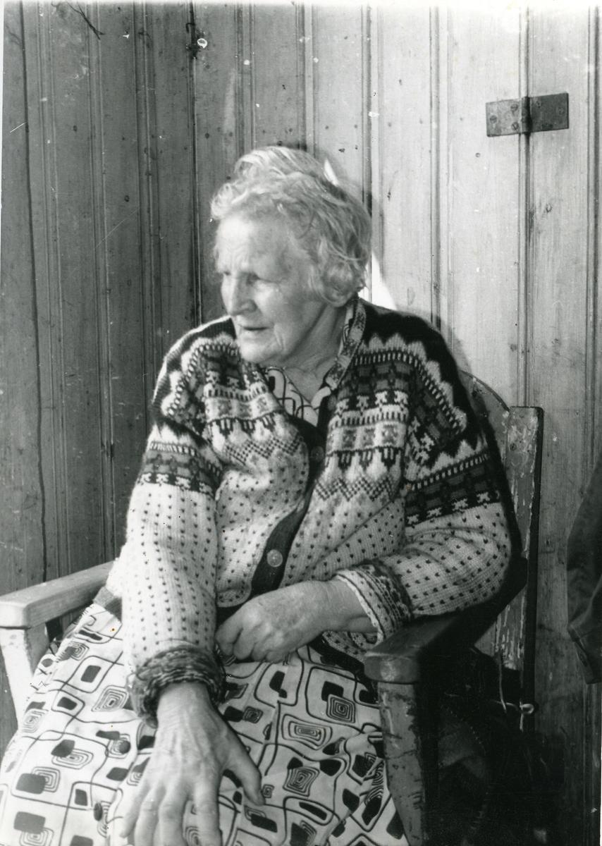 Portrett av Marie Brager sittende inntil en vegg.