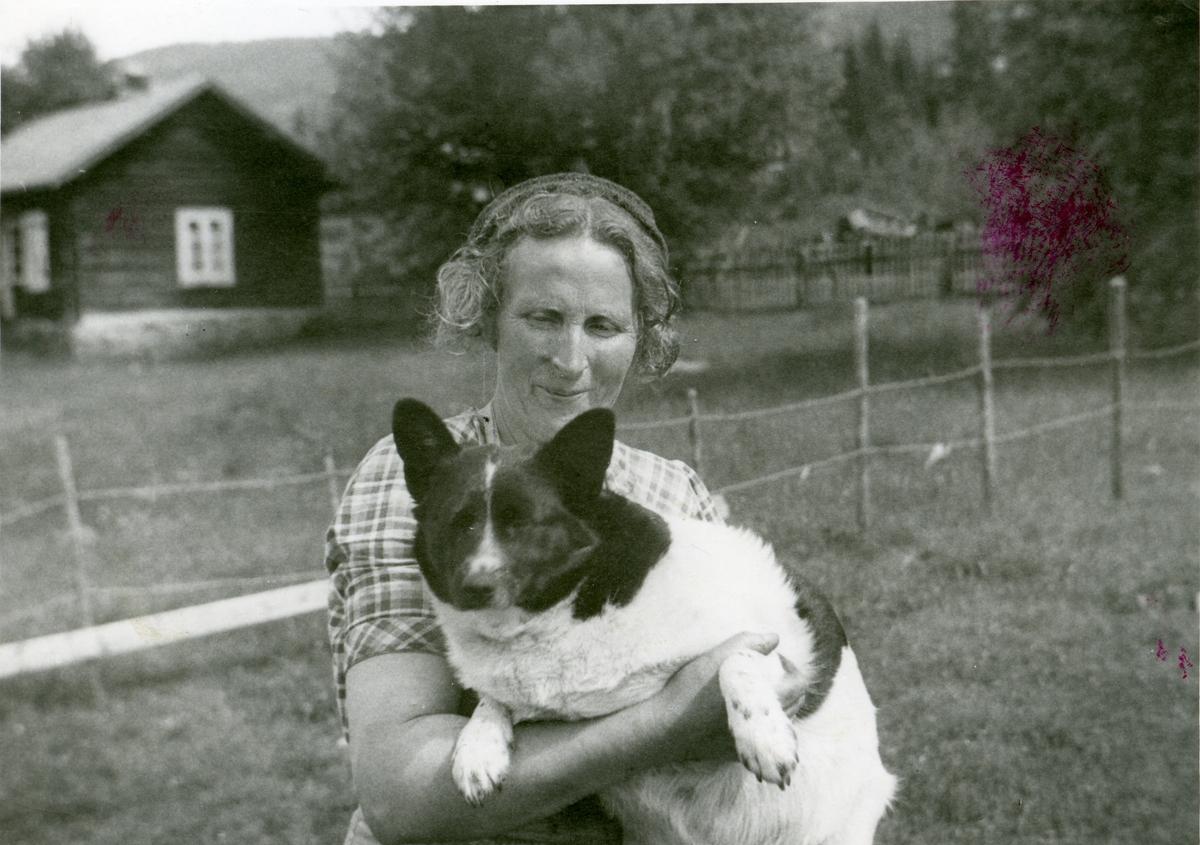 Marie Brager fotografert sammen med sin hund i hagen.