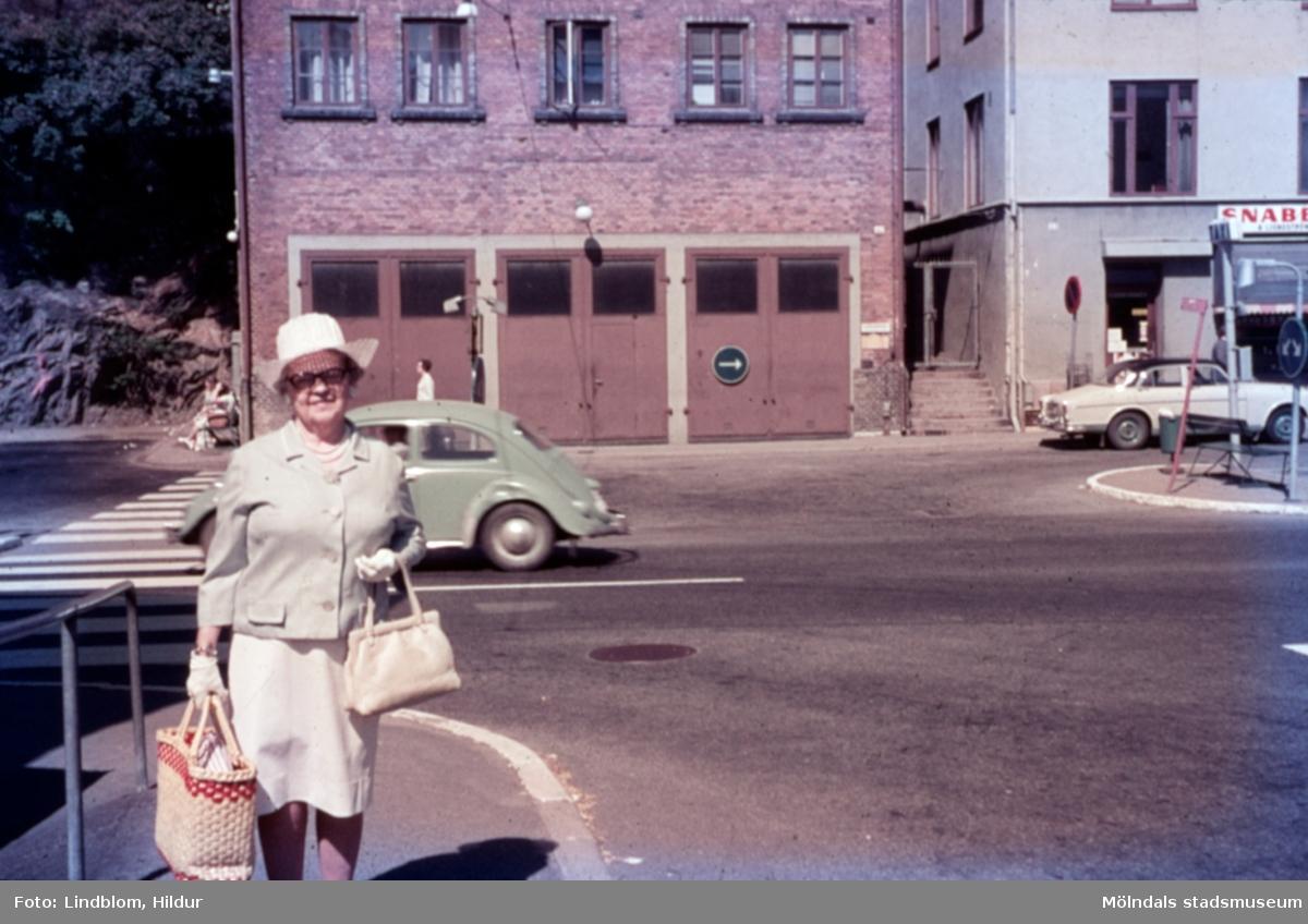 En kvinna vid Gamla Torget i Mölndal, 1970-tal. I bakgrunden ses Kvarnbygatan 41, tidigare brandstation och garage för polisbilar, numera Mölndals målarskola. Till höger ses del av huset Kvarnbygatan 43, tidigare Mölndals stadshus, sedermera musikskola.  För mer information om bilden se under tilläggsinformation.