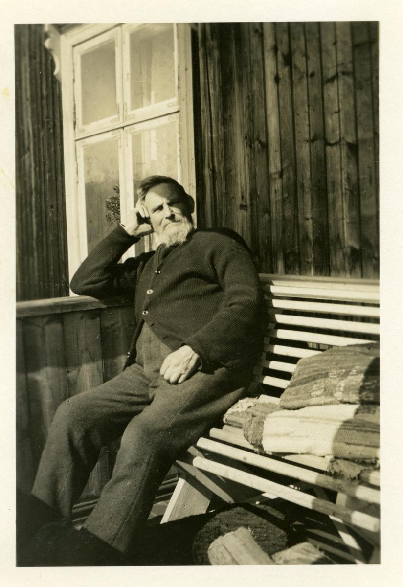 Hans Islandsmoen sitter på en benk foran hytta, sommeren 1932.