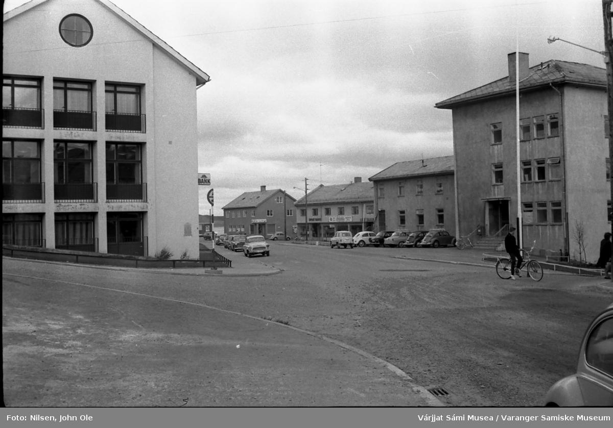 Gatebilde fra Vadsø sentrum. Bildet er tatt i krysset Havnegata/Tollbugata, bygningen til venstre er gamle Aust-Finnmark Sparebank, mens rådhuset er på høyre side. Butikker i bakgrunnen. 1967