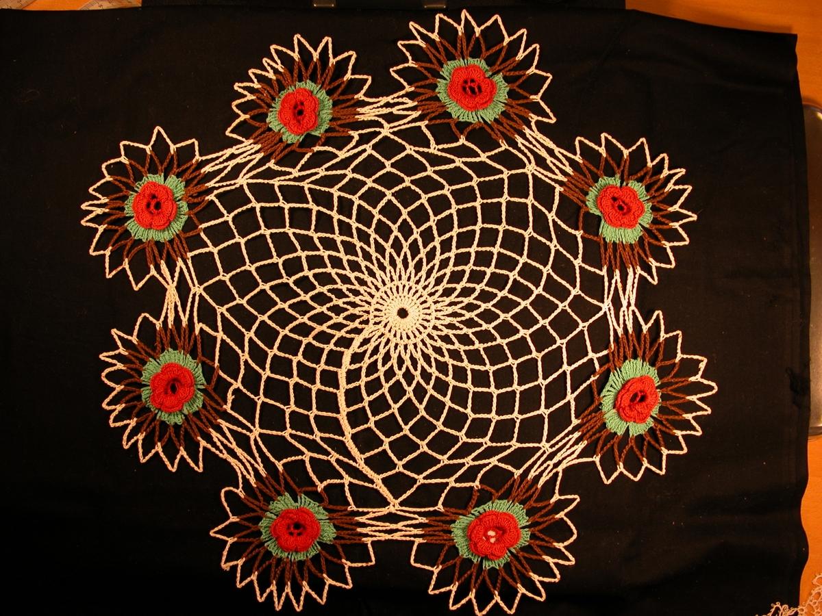 """fiskegarn""-motiv rundt i ein sirkel. 8 roser rundt kanten, der sjølve rosa er raud, blada er grøne, ein brun kant omkrinsar blada. Det er ein kvit kant rundt kvar blomst-emne."