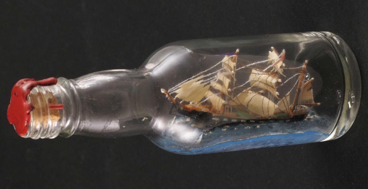 """Miniatyr flaskeskute: Bark  Glass, klart. Kork, rød lakk. Innstøpt i bunnen:  MG (Moss Glassverk)  Sort skrog med hvitmalte """"kanonporter"""". Blå sjø.  Utført av giver, hans nummer 84."""