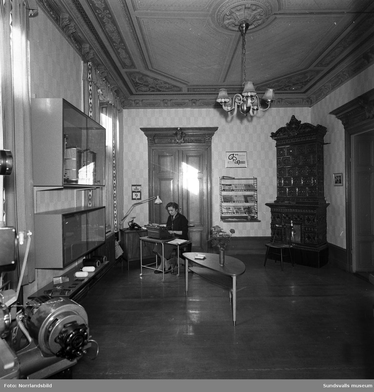 Thermia-Verken har kontor och utställningslokal i en vacker gammal våning på Tullgatan 7. Här samsas varmvattenberedare, värmepannor, montrar och stringhyllor med takmålningar, stuckatur och kakelugn.