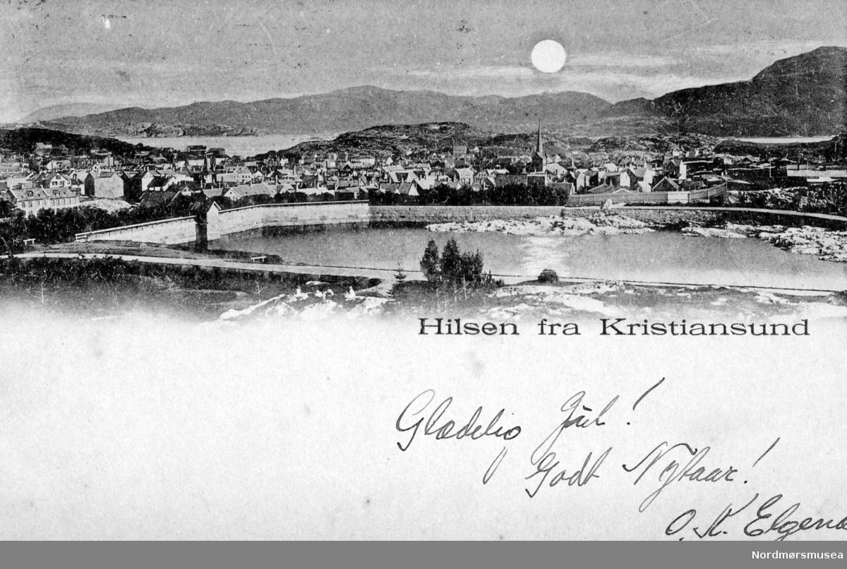Postkort/julekort fra Kirkelandet i Kristiansund, hvor motivet er fra Vanndamman. Datering er trolig fra tiden omkring åpningen av vannmagasinet ca. 1914. Fra Nordmøre museums fotosamlinger.