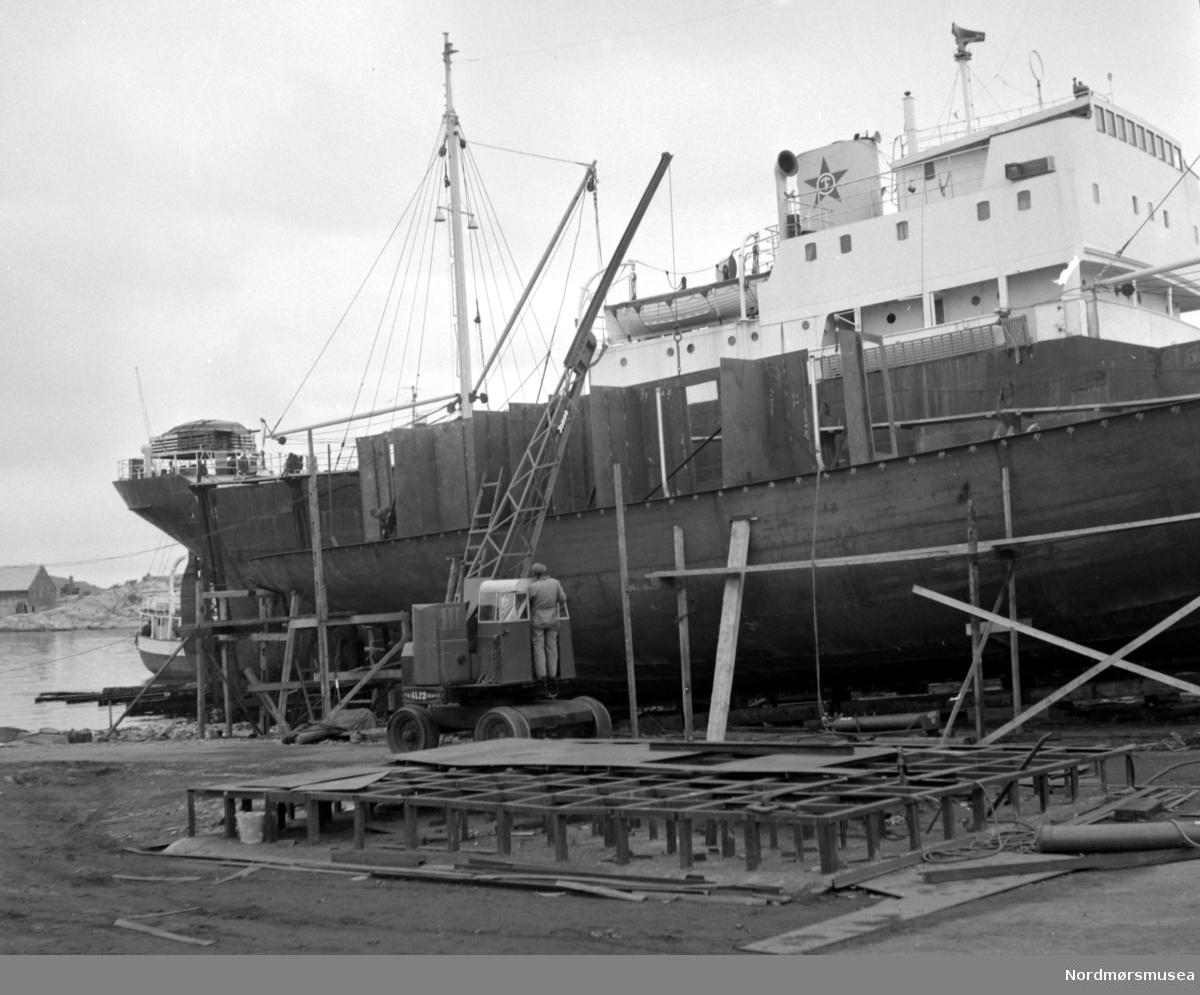 """Bildet viser M/S""""Knoll"""" fra Ole T. Flakkes rederi på den nye patentslippvogna, den største slippen mellom Bergen og Trondheim, klinkbygget i stål 1918 og erstattet med nytt slippanlegg ca. 1979. Foran ses B/F""""Norddalsfjord"""" Storviks Mek. Verkstedets bnr.14 på beddingen og reisingen av dekkshuset. """"Norddalsfjord"""" ble levert til Møre og Romsdal Fylkesbåtar 15. mars 1961 og hadde følgende hoveddimensjoner: L 31,20 m x B 8,55 m x D 3,35 m og hadde en tonnasje på 159 bruttoregistertonn. Fremdriftsmaskineriet består av 3 Volvo Penta turboladede dieselmotorer  type TMD96 på til sammen 420 hk som via kilremdrift var koblet til et felles gir og propellaksel med vribar propell, slik at hver enkelt av motorene kunne kjøres separat. Fergen hadde 2 Bolinders vekselstrømsaggregater type 1052MG på 23 hk hver tilkoblet en generator på 17 kW. Fergen var utstyrt med elektrohydraulisk styremaskin. Fergen har plass til 18 personbiler og har sertifikat for 160 passasjerer. Forut er det innredet 6 lugarer for offiserer og restaurant-personale og akterut en mannskapslugar for 4 personer og toppfarten er 11,4 knop og marsjfarten 10,5 knop.  Ferga er verkstedets første nybygg etter B/F""""Trygge"""" som ble levert i 1938.    I forgrunnen ses verkstedets mobilkran av fabrikat Jones KL22, og med forlenget egenlaget bom, som holder en stålplate på plass og ble anskaffet ca. 1959. På bakken ses sveiseplanet. Personen i mobilkrana er sjauer Gunnar Pedersen. Bak M/S""""Knoll"""" ses en båt som slipsettes på såpehellingen fra 1901 og bak ses også Høttneset og Høttnesbrygga. Bildet er fra 1960. Samme bilde som FAKf-100296.214954. Tekst: Peter Storvik. Fra Nordmøre museums fotosamlinger."""