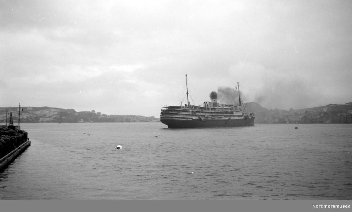 Turistbåten på bildet er franske M/S Foucauld på 11028 tonn, bygget for rederiet Compagnie des Chargeurs Reunis i 1923 som kombinert laste- og passasjerskip D/S L'Hoedic. Skipet ble ombygget til dieseldrevet turistskip i 1929 og gitt navnet M/S Foucauld. Skipet gikk tapt 15.juni 1940 i La Pallice etter et tysk flyangrep. (Info fra Espen Arnestad 2017). Ute i havnebasenget i Kristiansund ser vi en passasjerbåt gå ut, med Gomalandet til venstre i bakgrunnen og Nordlandet i bakgrunnen til høyre.  Serie. Fra Nordmøre Museum sin fotosamling.