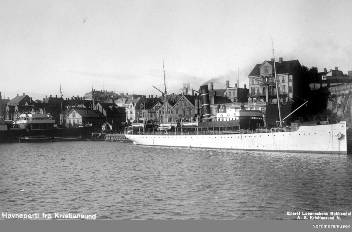 """Foto fra Kirkelandet i Kristiansund, hvor vi ser fra Kirkelandet Allmenning og dampskipkaia omkring 1920 til 1925. Her ser vi blant annet et stort dampskip liggende fortøyd ved Vågekaia ved Vågeveien. Muligens en av amerikalinjene. Utgiver av postkortet er Loennechens Bokhandel a.s, som trolig også er fotograf. ALTØ:  Antakelig Det Bergenske Dampskipsselskaps passasjerskip """";IRMA""""; som senere gikk inn i hurtigrutefart, ved kai i Kristiansund.  Her ved Vågekaia med Farstad-gården ovenfor på Haugan.  Mange av skipene endret farge fra hvit til sort og det ble også foretatt ombygginger.  Her ser vi  båten er hvit, men den endret senere til svart.  """";Irma""""; ble levert i april 1905 fra Sir Raylton Dixon & Co. Ltd. i Middelsbrough, og representerte toppen i utviklingen av de kombinerte turist-, passasjer- og godsruteskip. Den hadde sertifikat for 230 passasjerer og gjorde 13,5 knops fart. """";Irma""""; ble primært bygget for Englands-ruten. I sommersesongen ble den også benyttet i turistruten til Vestlandsfjordene. Bergenske og Nordenfjeldske markedsførte seg i utlandet som """";B & N Line Royal Mail Ltd. Nordenfjeldske trakk seg ut og i stedet ble """";Irma""""; i sommermånedene anvendt som turistskip sammen med dampyachten """";Meteor"""";. """";Irma""""; seilte i 1920-årene i forskjellige av selskapets ruter. Rundt 1930 gjennomgikk skipet en grundig moderisering. Den var 26 år gammel da den ble satt inn i hurtigrutedrift hvor den seilte i mange år. Den slapp heldig fra krigshandlingene i 1940 og ble om sommeren på ny satt inn i ruten, men ble alledrede om høsten rammet av krigsforlis. Den fortsatte i videre drift, men kvelden 13. februar 1944 var det slutt. Den hele endte tragisk da ble senket av en norsk MTB like nord for Hestskjæret på Hustavika på vei nordover. Marinefartøyet antok at den var i tysk tjeneste, siden det var utstyrt med luftvernkanoner, og identifiserte ikke skipet før angrepet. 36 av besetningen og 25 passasjerer ble drept. Bare 25 overlevde dette kanskje mest tragiske av alle"""