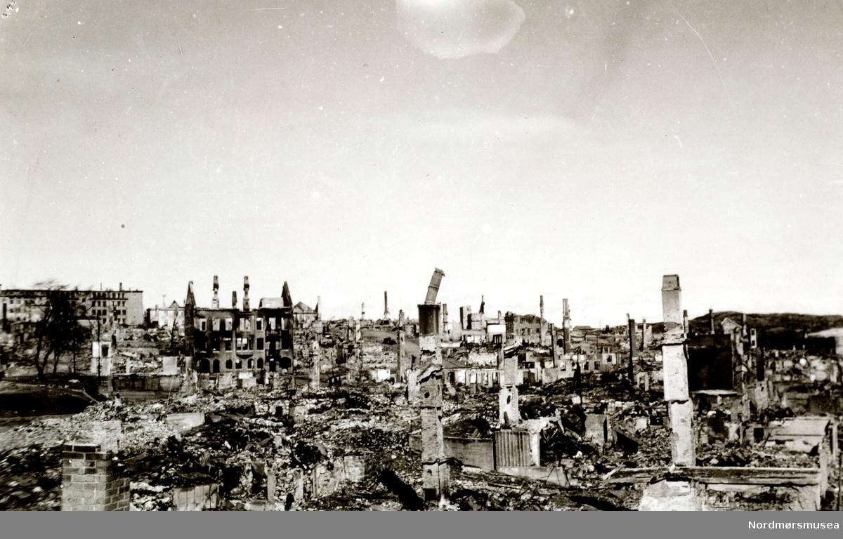 """Krigen har her kommet til Kirkelandet i Kristiansund. Etter nazistenes herjinger i perioden 28. april til 1. mai 1940 ligger nå store deler av byen i ruiner. Her ser vi fra noen av ruinene i sentrum. Det totale antall brente bygg var 767, hvor 605 av disse var på Kirkelandet og 162 på andre """"land"""" i Kristiansund. Her fantes det til blant annet til sammen 3906 boliger ifølge boligtellingen av 1938, og av disse brant 2162 boliger ned og 7099 mennesker ble husløse. I tillegg til de 767 brente byggene brant 36 fiskepakkehus ned til grunnen, hvorav 34 lå på andre """"land"""". Verdien av de brente byggene beløp seg til kroner 26,9 millioner for Kirkelandet (kroneverdi per 1940) eller tilsammen 30,6 millioner kroner (kroneverdi per 1940) for hele byen. Fra Nordmøre Museums fotosamlinger. Kilde: Gjenreisningsproblemer i Kristiansund. Fremlagt ved gjenreisningsinstituttet i Kristiansund, juli 1945, side 16. EFR2015"""