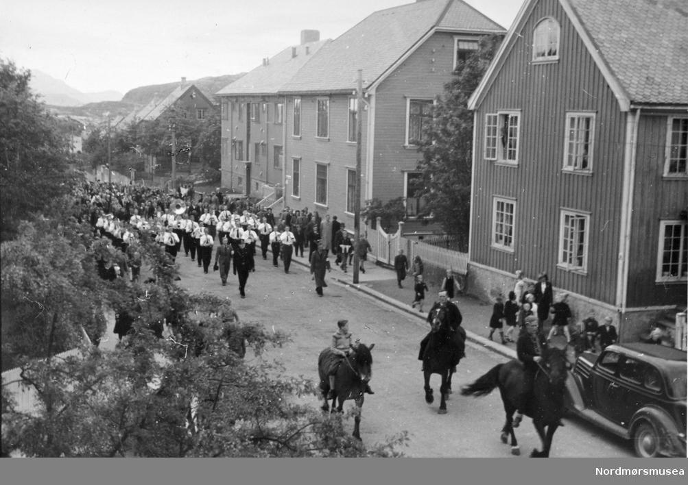 I hjørnet en Ford V8 1935. (info: Ivar Stav ) -På baksiden av fotoet står notert:  Tollinspektør Flors gate i 1945? Frigjøringsfeiring? Fremst i toget ser vi to personer som har armbind. Serie på 3