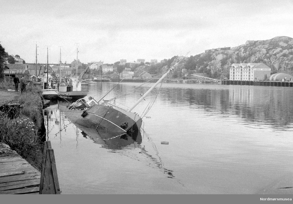 """bilde nr 2 av samme: Fartøyet er dampskonnerten """"Værdalen"""", bygget i 1892 på Trondhjems Mek Verksted for AS Værdalsbruket, Verdal, som transportbåt på Trondheimsfjorden. Opprinnelig bygget som et hybridskip med en 49/34 compound dampmaskin, senere byttet ut til større dampmaskin flere ganger. I 1954 ble det satt inn en 220hk GM diesel. Brukt i rutefart og deretter fraktfart.Ut av fart i siste del av 70-tallet. Bildet er sannsynligvis tatt i perioden 1966 til 1972 hvor den var i eie i Kristiansund. I 1971 ble den tatt ut av bruk, og i 1981 ble den kjøpt av Olav T Engvik som begynte et restaureringsarbeid som ble fullført i 2015.  Her halvveis nedsunken i Vågen i Kristiansund. Repotasjebilde, Romsdalspostens arkiv. Fra Nordmøre Museum sin fotosamling."""
