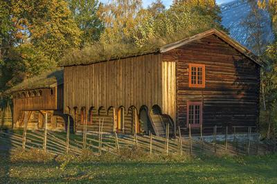 Grimsrudbygningen på Hedmarkstunet er en brunlig toetasjers tømmerbygning med to rutete vinduer over hverandre i gavleveggen og tettet svalgang i andre etasje.. Foto/Photo