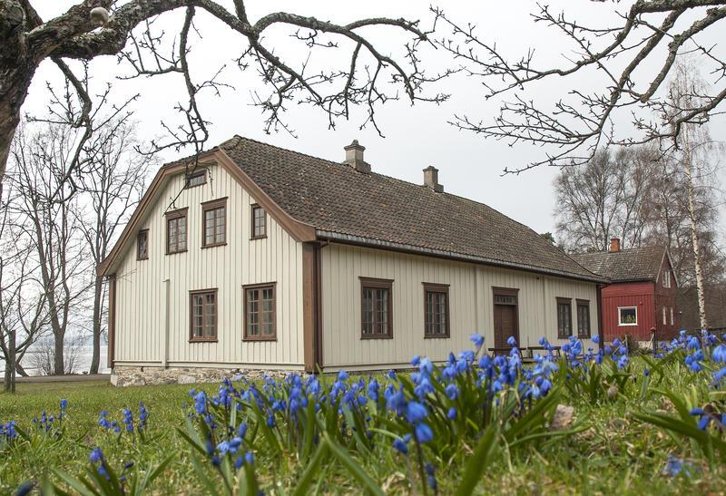 Hvitt hus med valmet tak og blå blomster i forgrunnen. (Foto/Photo)