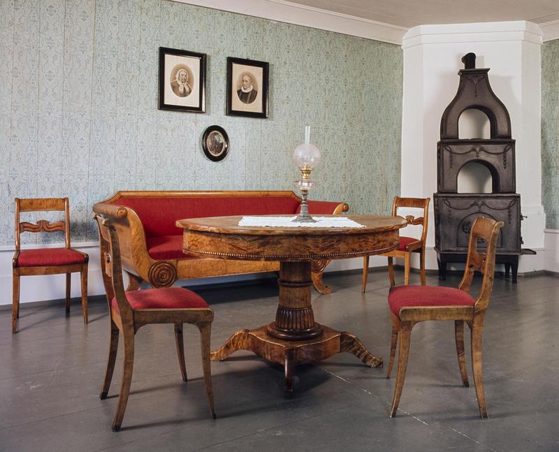 Interiør; brunt bord med stoler og sofa i samme treverk og med rødt trekk, to gamle fotografier på veggen og en etasjeovn i støpejern. (Foto/Photo)