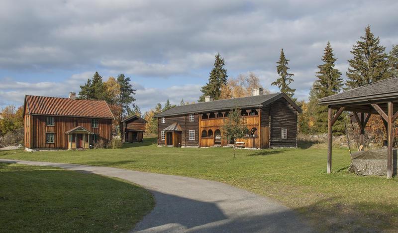 Grusveg som fører over et tun med en låve lengst til høyre, samt to brunlige tømmerbygninger hvorav det ene med svalgang. (Foto/Photo)