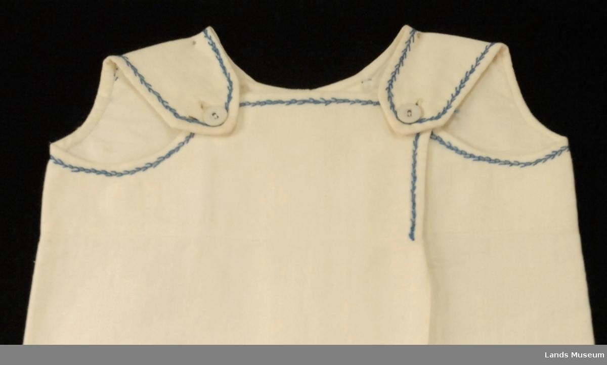"""Brodert med blå bomullstråd i sik-sak mønster langs erme og halskant. """"Selene"""" holdt sammen på skuldrene med stofftrukket knapp på hver side. Foret bærestykke. Foret er sydd på med søm under ermeåpningen. Bakdelen knappes på. Foran fold - nedsydd i bærestykket.   Hjemmesydd og ubrukt."""