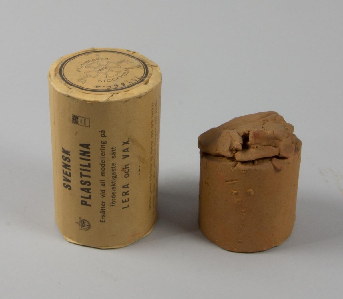 Plastelinamaterial, 6 st. 4 st cylindriska i obrutna förpackningar med brunt omslagspapper och lång reklamtext. 2 st utan omslagspapper och använda till häften. Ovanpå en av dem klumpar av plastelina.